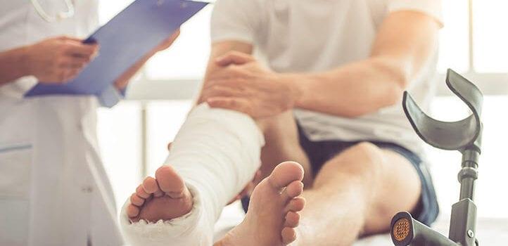 Mężczyzna z nogą w gipsie rozmawia z pielęgniarką