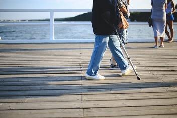 Mężczyzna podparty na kuli spaceruje po molo
