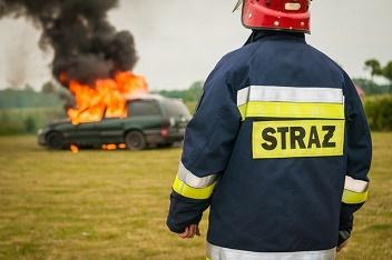 Strażak patrzy na płonący samochód