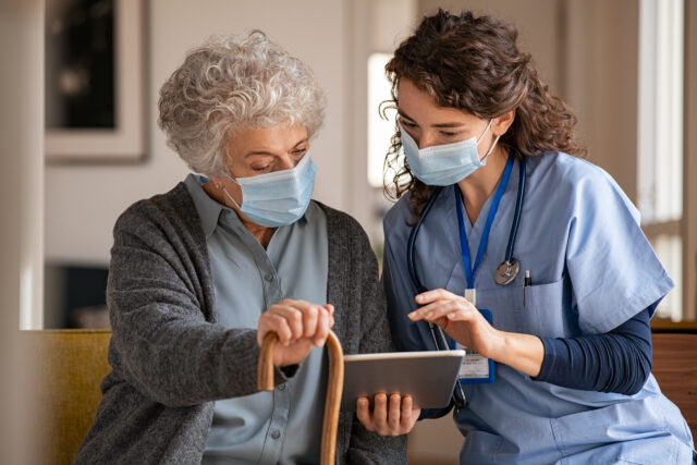 Senior woman and nurse using digital tablet at home during consult